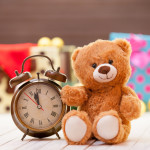Alarm clock and teddy bear on christmas background