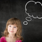 Smart kid in class. Happy child against blackboard. Drawing speech bubble cloud