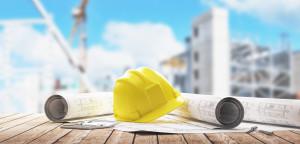 Elmetto giallo operaio con progetti cantiere
