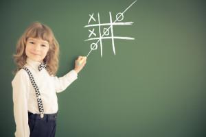 School kid in class. Happy child against green blackboard. Education concept