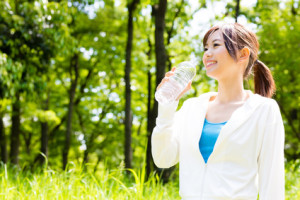 young asian woman with drinking water in the park