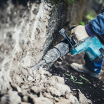 Industrial equipment close up. Construction worker using pneumatic machinery, drilling tool