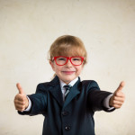 Portrait of young happy businessman showing thumbs up. Success and creative concept. Copy space for your text
